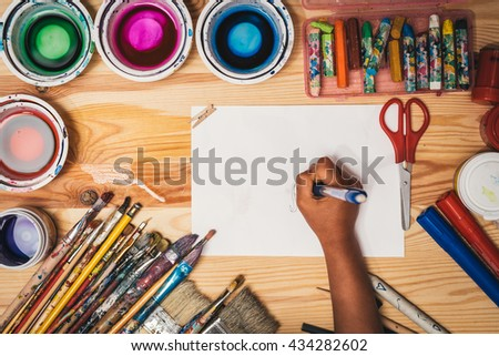 child's hand drawing at painting workshop. Painting tools on wooden board with sheet of white paper. Used colorful paintbrushes and crayons. - stock photo