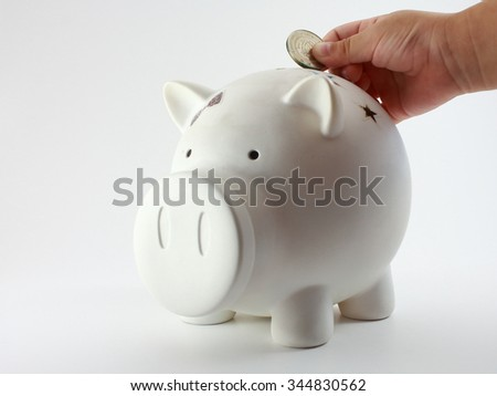 Child's Hand Drop A Coin In Piggy Bank