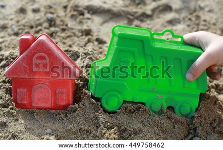 Child's hand holding a toy lorry, truck in the sandbox. Bright plastic toys in the sandbox or on the beach. Sandbox, background, children, hand, auto, home, house, buy, purchase, housing, business. - stock photo