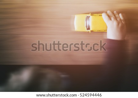 Child's hand holding a yellow toy car, wood, table