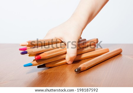 Child's hand holding many colored pencils - stock photo