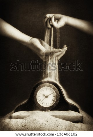 Child's hand passing sand to an adults hand dropping sand onto a clock covered in sand - stock photo