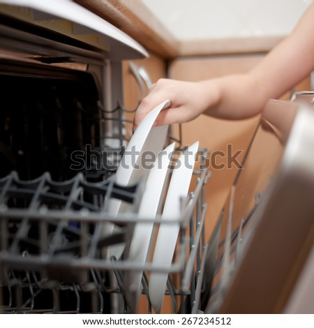 Child's hand putting a plate in the dishwasher. Kids housework. - stock photo