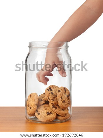 Child's hand reaching out to take cookies from a jar  - stock photo