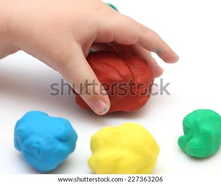 Child's hand take red plastic clay ball. White background. - stock photo