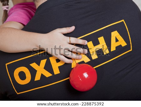 "Child's hand with a toy on the back of a man in a t-shirt with the words ""Protection"" in Russian - stock photo"