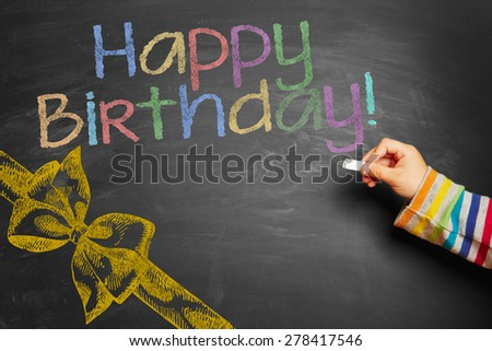"Child's hand writing a colourful ""Happy Birthday!"" on blackboard - stock photo"
