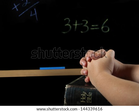 child's hands folded in prayer on a Holy bible with chalkboard - stock photo