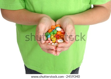 Child's hands holding a handful of lollies / candy. - stock photo