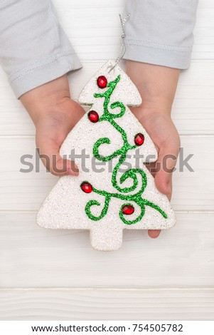 Child's hands holding ornamental christmas tree on white table. Flat lay, top view
