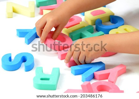 Child's hands playing with alphabet blocks