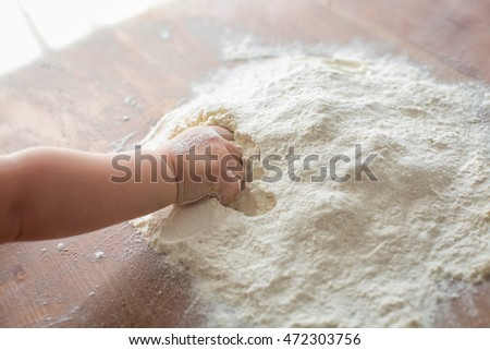 Child's hands playing with the flour