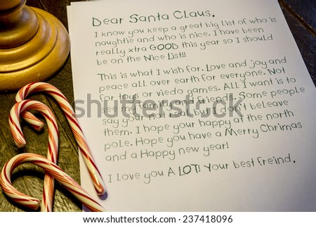 Child's letter to Santa Claus written with green pen sitting under lamp on wooden table with red and white candy canes - stock photo