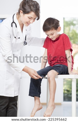 Child's neurologist testing knee reflex of young patient - stock photo