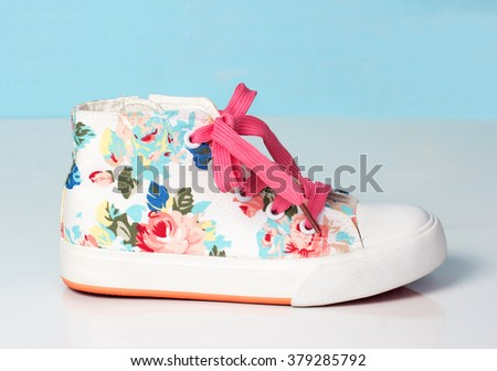 Child's textile lace sneakers single shoe on soft blue background.Fashion kid's footwear. - stock photo