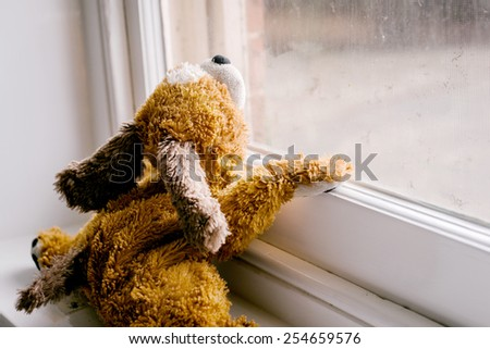 child's toy looking out the window - stock photo