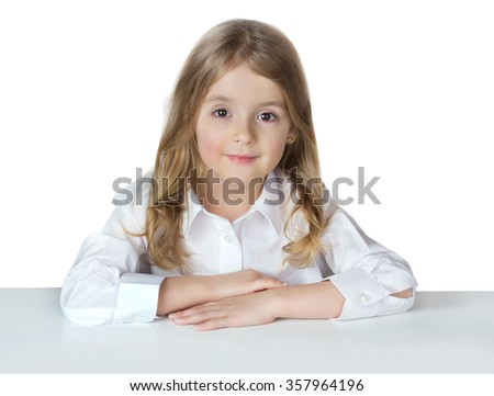 Child school girl in white shirt sitting at table.Pupil female kid isolated on white.Primary education. - stock photo