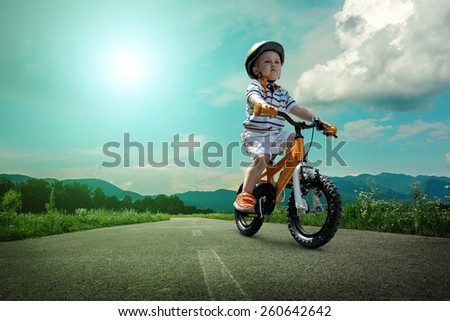 Child seating on the orange bicycle and travelling on the non-urban road under sky - stock photo