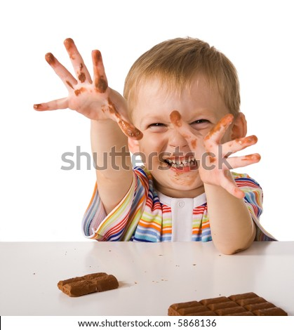 Child shows hands smeared by chocolate - stock photo