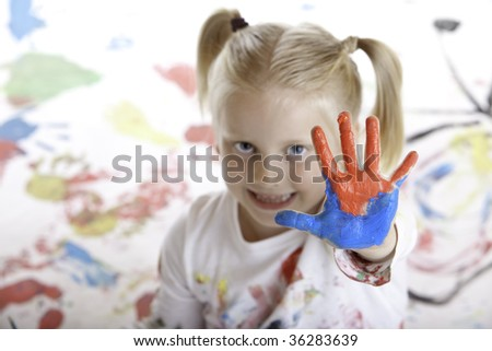 child shows her painted hand during painting session - stock photo