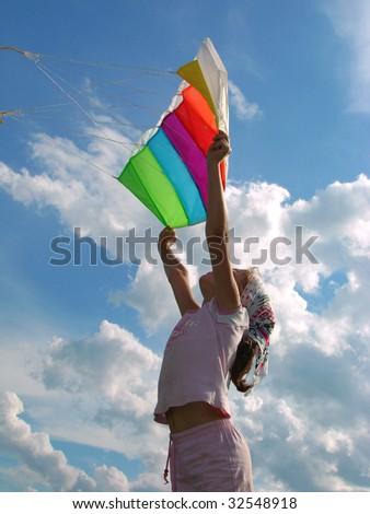 child silhouette start flying kite against cloudy sky - stock photo