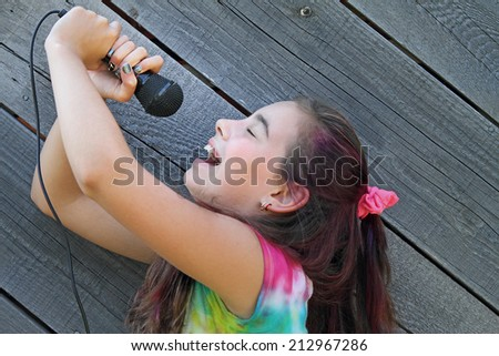 Child singing into microphone with pink hair and tie dye shirt. - stock photo