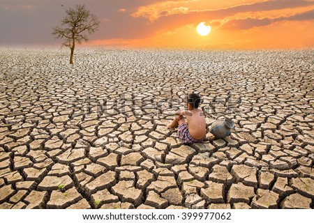 Child sit on cracked earth in the arid area