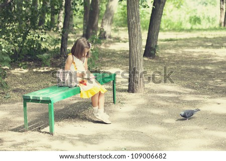 Child sit on the bench in the park. - stock photo