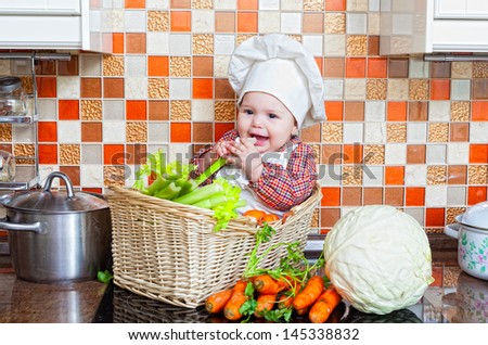 Child sits in a wattled basket on a table with vegetables - stock photo