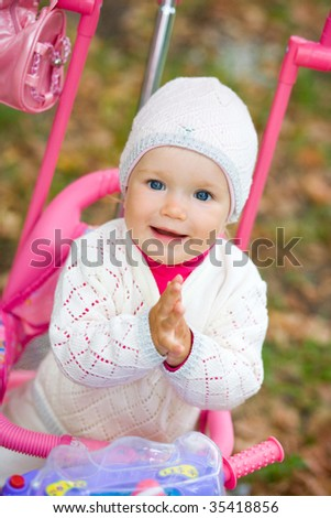 Child sits on a tricycle. Slaps hands together - stock photo