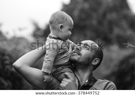 child sits on dad's shoulder and smiling. black and white a photo - stock photo