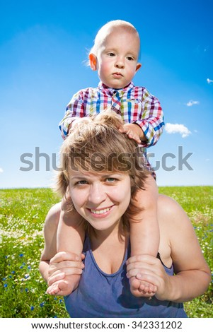 child sits on his mother's shoulders - stock photo