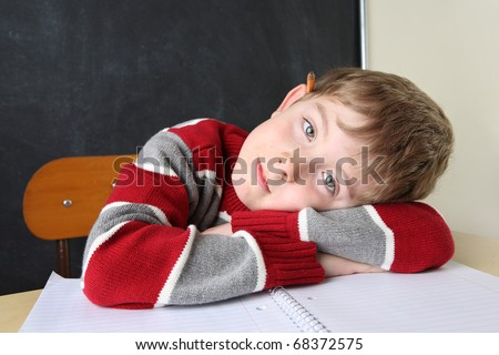 Child sitting at a desk laying his head on his arms - stock photo