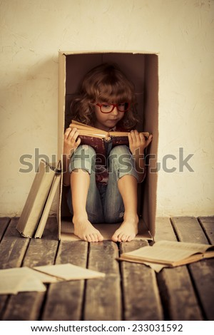 Child sitting in cardboard box. Kid reading book. Freedom and imagination concept. Unusual portrait