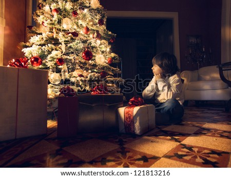 Child sitting near a Christmas tree