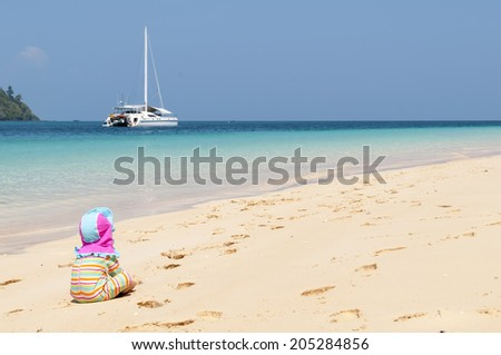 child sitting on a beach, sailboat in the background