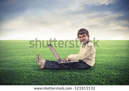 Child, sitting on a lawn, using a laptop computer - stock photo