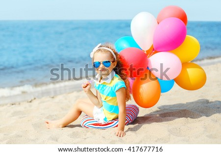 Child sitting on beach with colorful balloons near sea summer day - stock photo