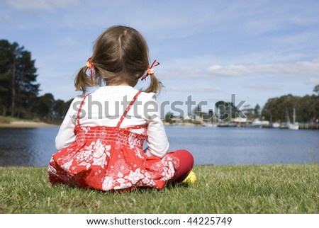 Child sitting on grass looking at boats on lake. Horizontally framed shot.