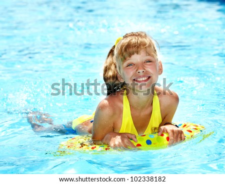 Child sitting on inflatable ring in swimming pool. - stock photo
