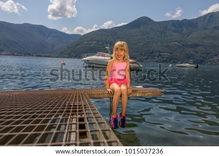 child sitting on the jetty at the Lago Maggiore in Italy and having family vacation