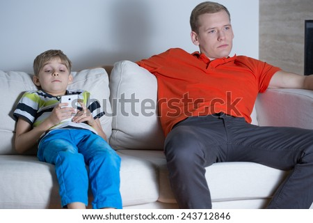 Child sitting on the sofa and using smartphone - stock photo