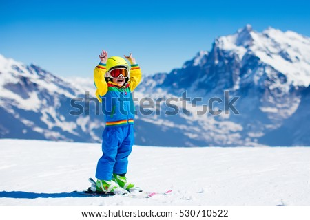 Child skiing in mountains. Active toddler kid with safety helmet, goggles and poles. Ski race for young children. Winter sport for family. Kids ski lesson in alpine school. Little skier racing in snow