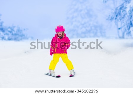 Child skiing in the mountains. Toddler kid in colorful suit and safety helmet learning to ski. Winter sport for family with young children. Kids ski lesson in alpine school. Snow fun for little skier. - stock photo