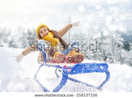 Child sledding. Little girl enjoying a sleigh ride. Child girl riding a sledge. Child plays outdoors in snow. Outdoor fun for family winter vacation. - stock photo