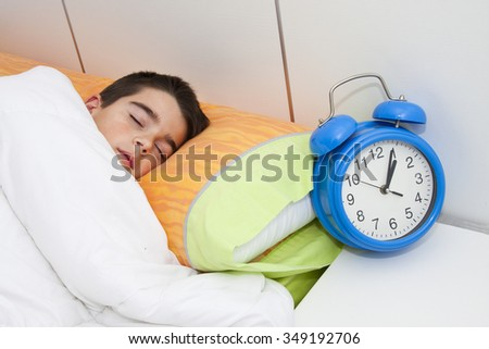 child sleeping in bed with alarm clock - stock photo