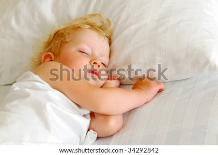 Child sleeps in bed - stock photo