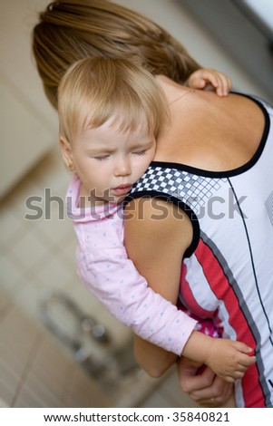 Child sleeps on a shoulder at mother - stock photo