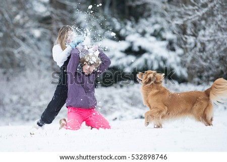 Child smashing snowball over another kids head during a white wi