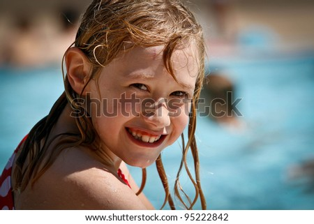 child smiling at the side of a swimming pool with wet hair - stock photo